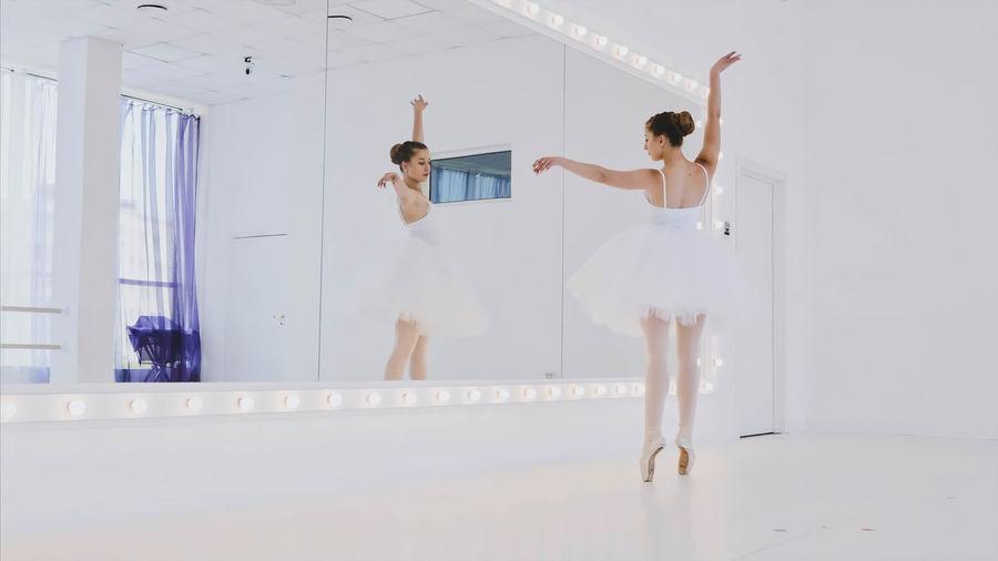 Ballerina looking in mirror while dancing at studio