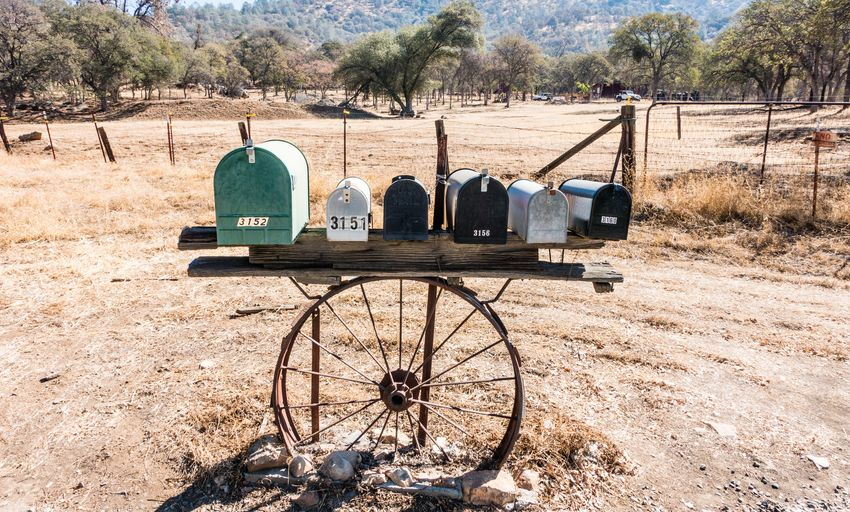 Land Tree Plant Field Nature Landscape Day Sunlight Environment No People Outdoors Old Wheel Non-urban Scene Abandoned Tranquility Rural Scene Scenics - Nature Sunny Obsolete Arid Climate Mailbox Public Mailbox Letter