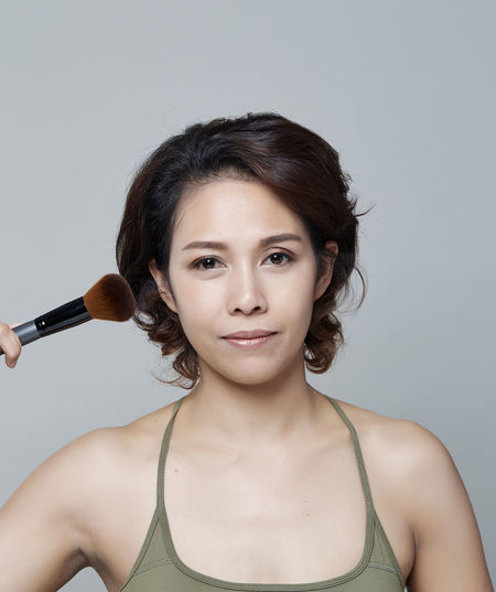 Portrait of smiling beautiful woman holding make-up brush against gray background