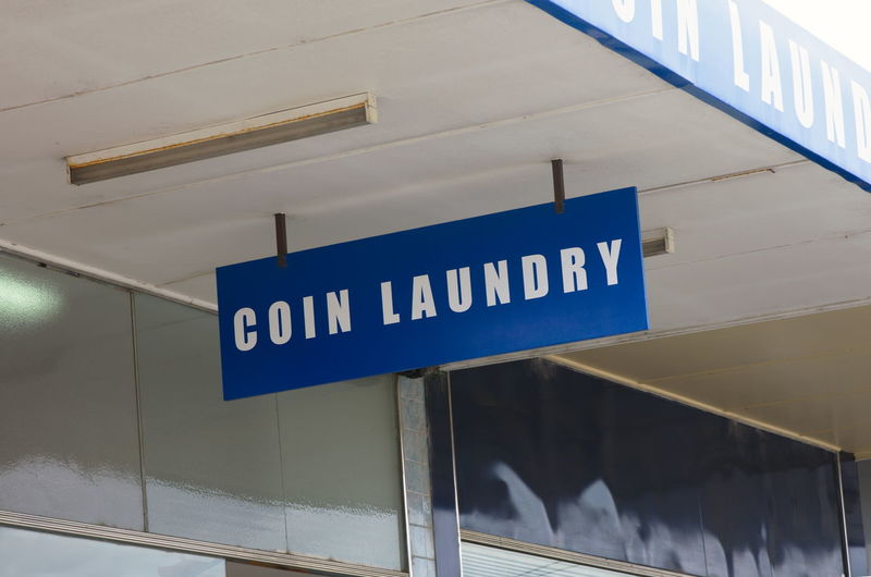 Laundry Sign Architecture Arrow Symbol Blue Building Exterior Built Structure Close-up Coin Communication Day Direction Guidance Indoors  Low Angle View Nameplate No People Parking Garage Road Sign Text Western Script