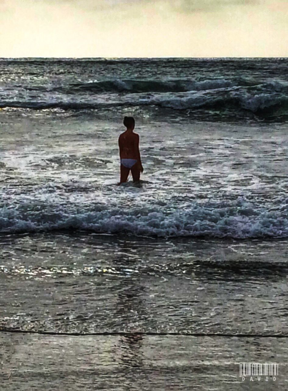 sea, water, real people, nature, one person, beach, beauty in nature, outdoors, rear view, standing, shirtless, sunset, vacations, lifestyles, wave, scenics, leisure activity, full length, ankle deep in water, men, boys, day, sky, horizon over water, people