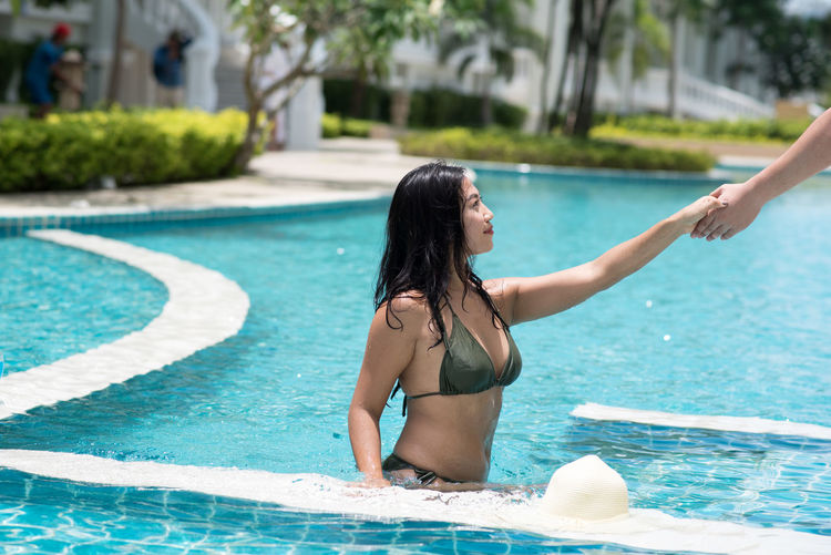 Cropped hand assisting young woman out of swimming pool