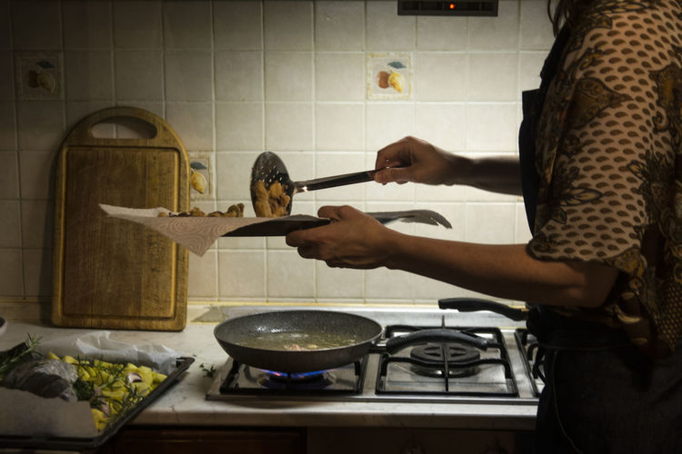 Midsection of woman preparing food in kitchen