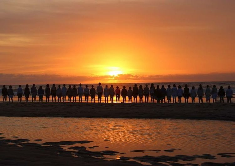 People Standing In Row On Beach During Sunset