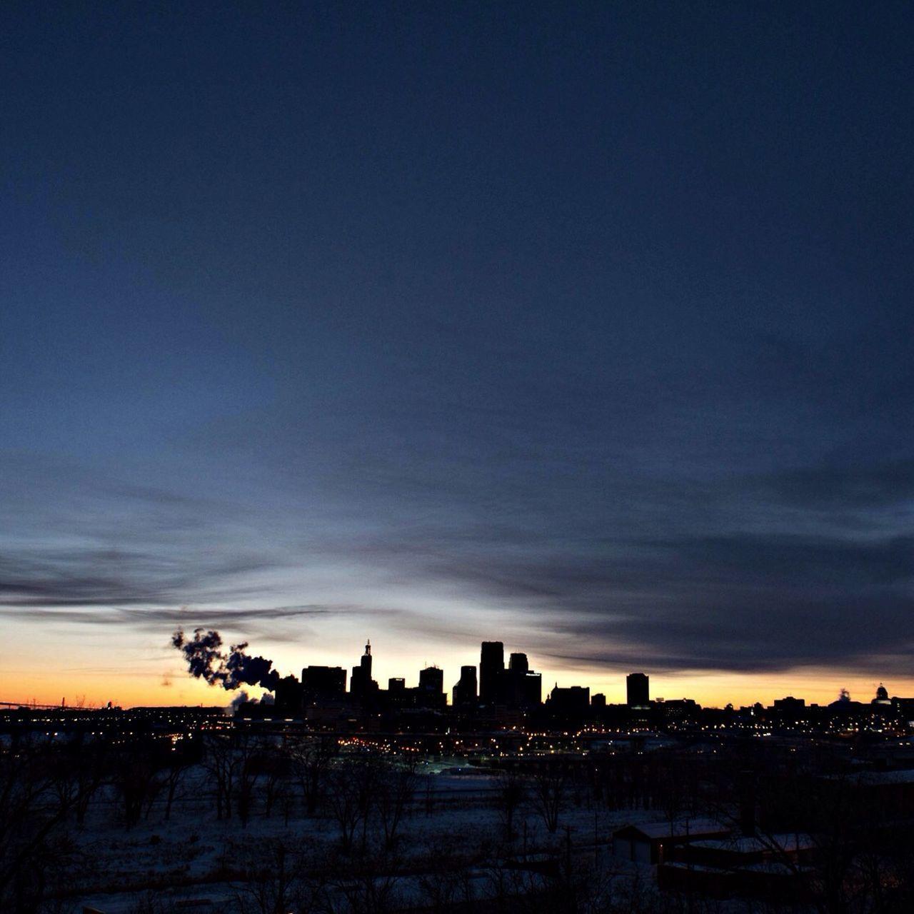 Silhouette cityscape against sky at dusk