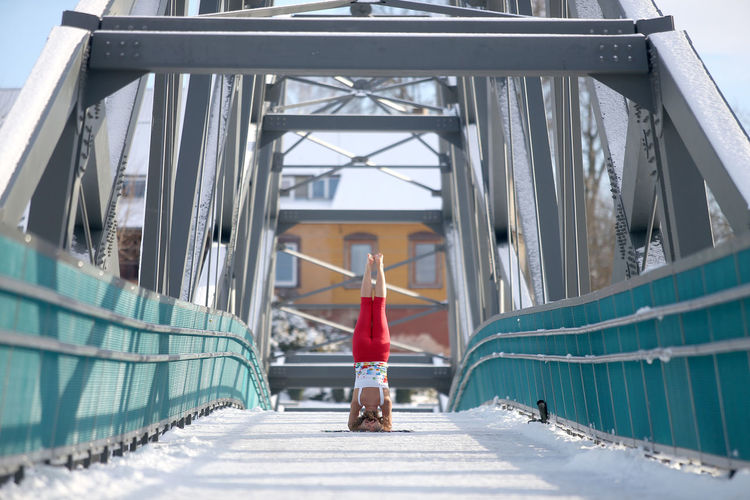 Rear view of woman doing headstand on bridge
