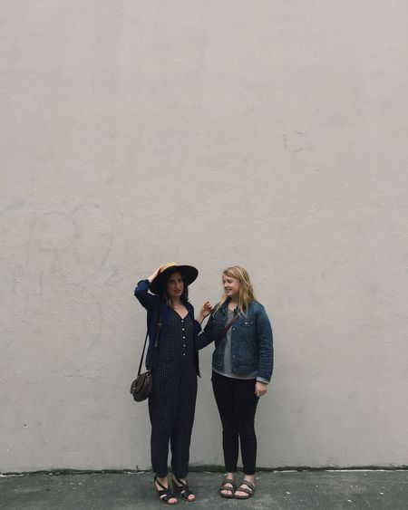 Full length of female friends standing on sidewalk against beige wall