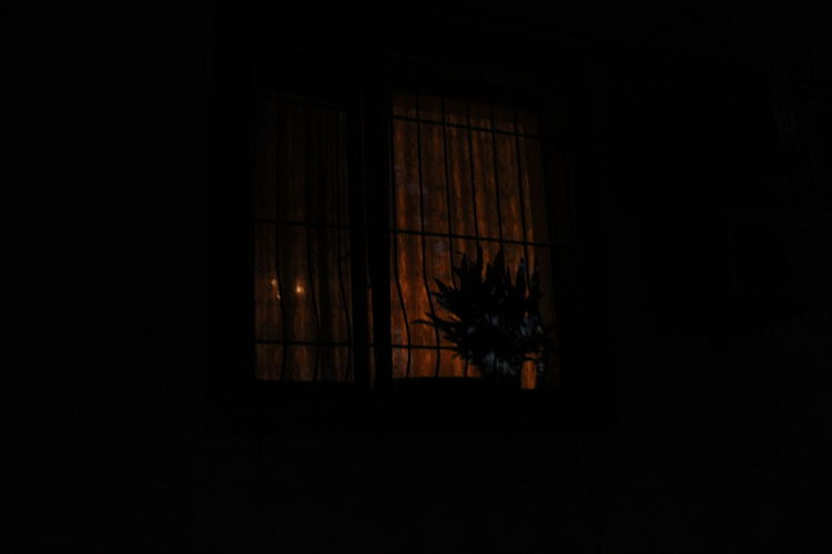 Silhouette of building seen through window at night