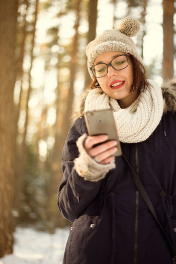 Cold Temperature Communication Eyeglasses  Front View Happiness Holding Knit Hat Mobile Phone One Person Outdoors Portable Information Device Real People Scarf Smart Phone Smiling Snow Standing Technology Text Messaging Using Phone Warm Clothing Winter Wireless Technology Young Adult Young Women