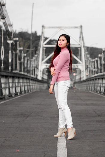 Portrait of woman standing on bridge in city