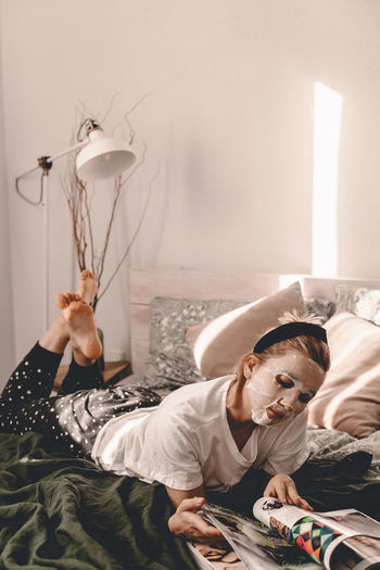 Woman with face mask reading book while lying on bed