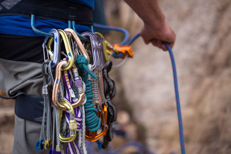 A rock climber belays his partner using ropes and climbing equipment Adventure Belayer Belaying Carabiners Climbing Climbing Equipment Climbing Rope Close-up Day Equipment Extreme Sports Focus On Foreground Hand Holding Human Body Part One Person Outdoors Real People Rock Climbing Rope Safety Safety Equipment Safety Harness Sport Strength
