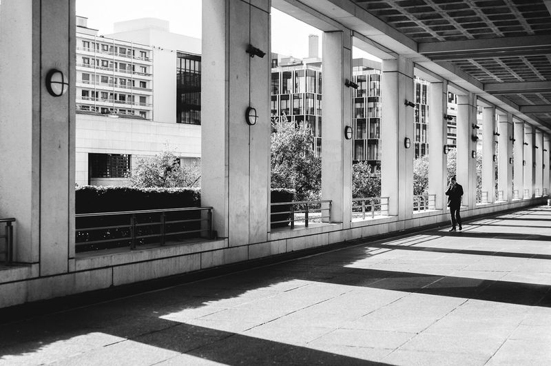 In the shadow Architecture Built Structure Building Exterior Walking Real People Day One Person Men Outdoors City Light And Shadow Shadow Shadows & Lights People Architecture Architectural Column Shadows Nikon Nikonphotography Paris City Paris, France  Exploring Photooftheday Photographer