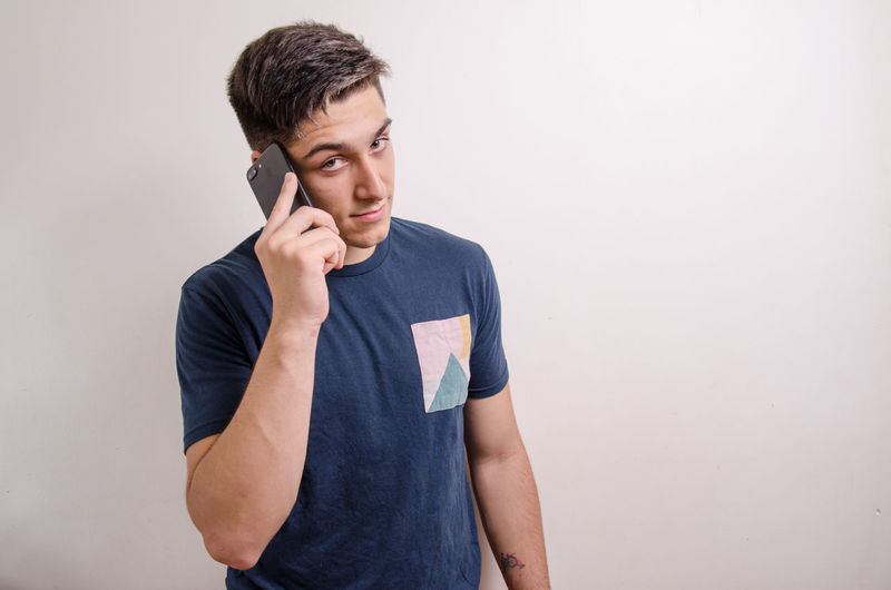 Young man using phone while standing against wall