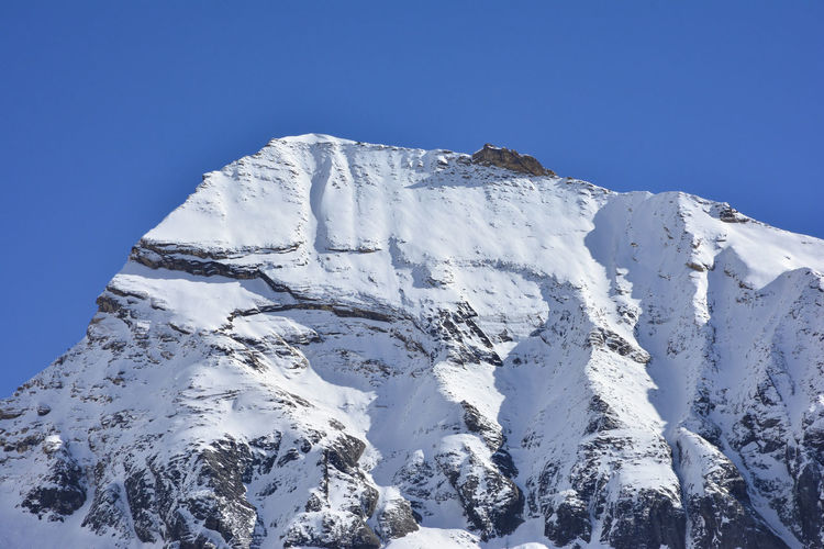 Low angle view of snowcapped mountains against clear blue sky, annapurna