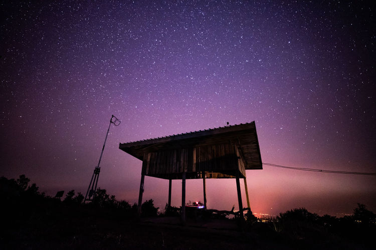 Low angle view of silhouette built structure against star field sky at night