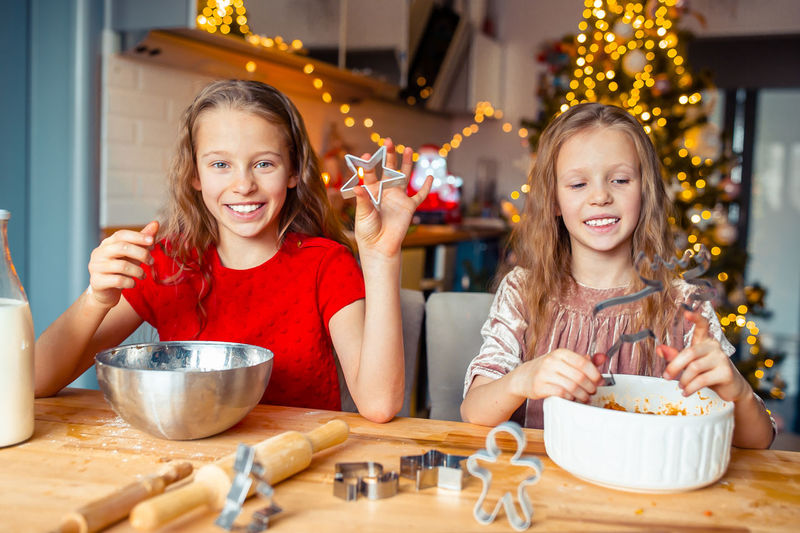 Portrait of smiling girl with sister making christmas cookies at home