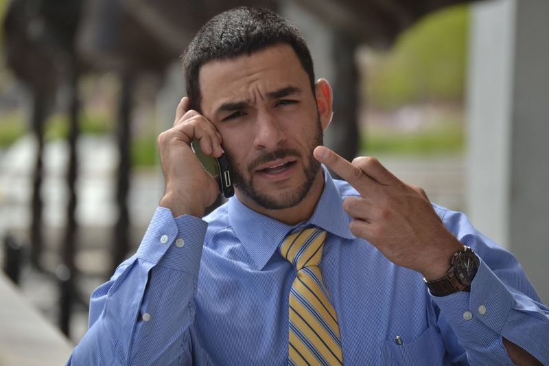Portrait of businessman showing obscene gesture while talking on mobile phone