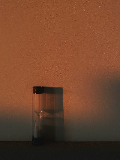 Close-up of glass on table against wall