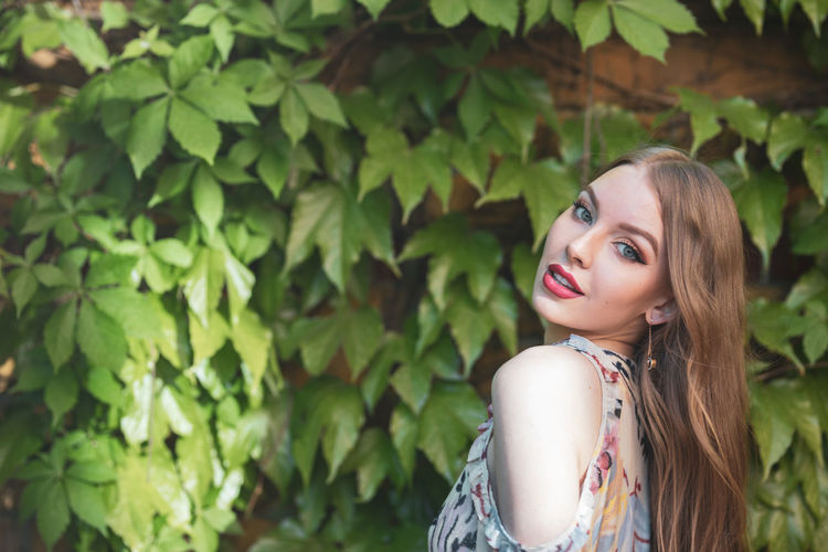 Portrait of beautiful young woman standing by plants in park