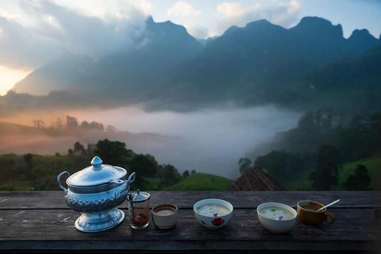 Tea cup on table against mountains