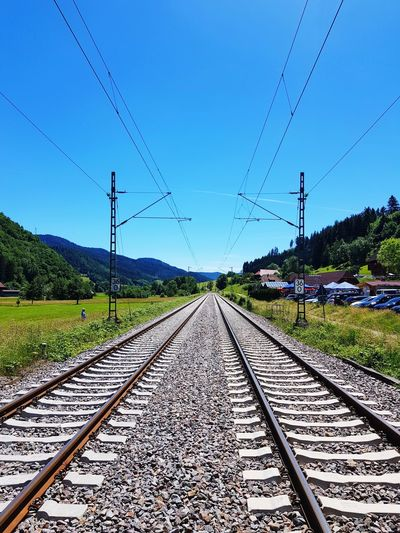 Railroad tracks against clear blue sky