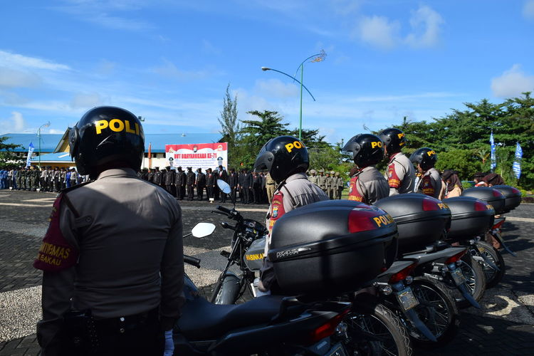 Police with motorcycles standing on road during event