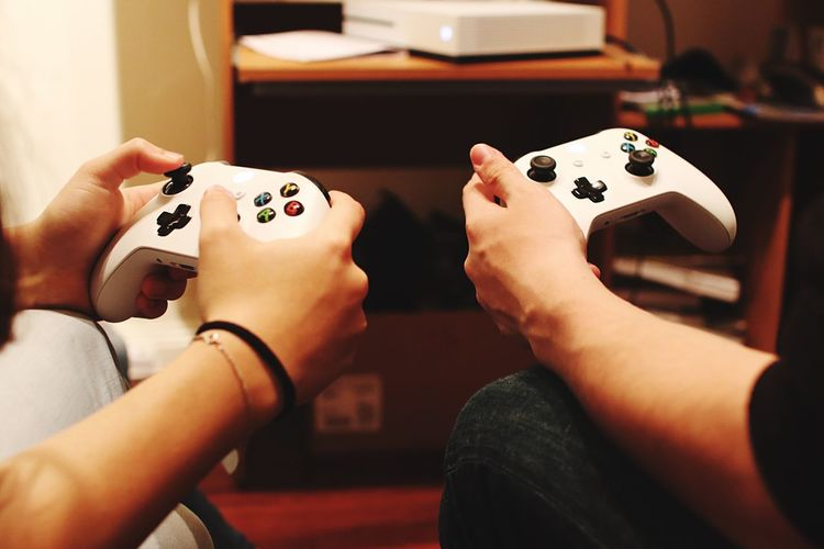 Cropped Hands Of Friends Playing Video Game At Home