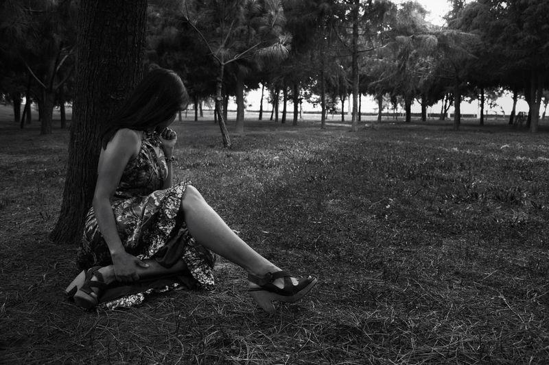 Woman sitting on field in park