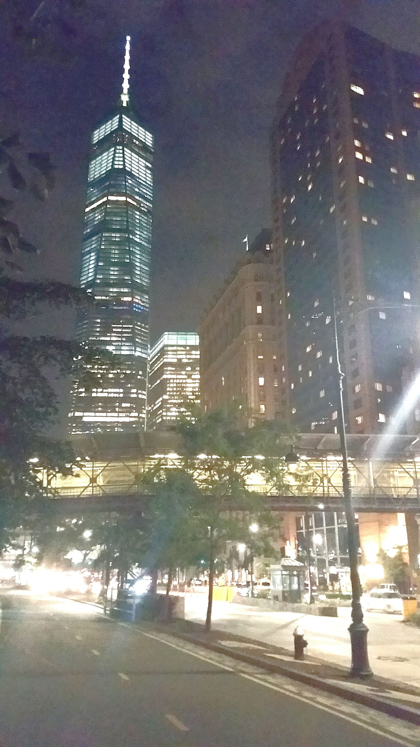 architecture, building exterior, built structure, skyscraper, tower, city, tall - high, illuminated, night, modern, office building, travel destinations, low angle view, city life, urban skyline, sky, spire, cityscape, financial district, tourism, growth, building story, outdoors, capital cities, famous place, development, tall