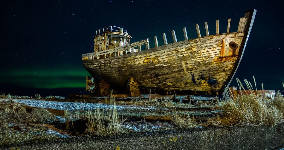 Abandoned ship at beach at night