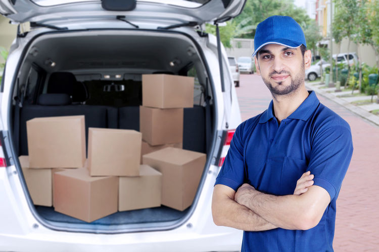 Portrait of smiling man standing against cardboard boxes in car on street