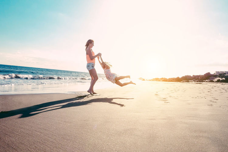 Mother and daughter having fun on tropical beach Freedom Happy Holiday Love Mother SPAIN Vacations Young Youth Beach Daughter Fun Lifestyles Outdoors People Playing Sea Summer Sun Sunlight Sunset Vacations Water Women Capture Tomorrow
