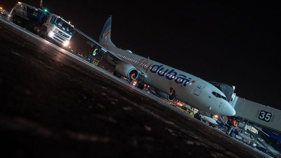 Airplane on runway against clear sky at night