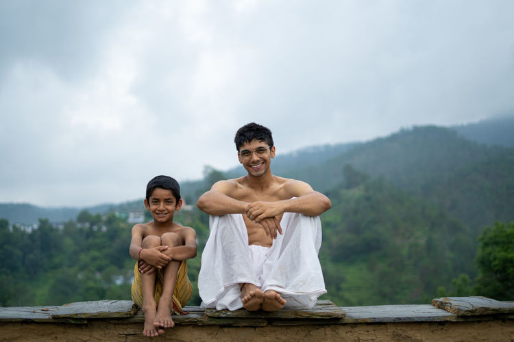 Portrait of friends sitting on rock against sky