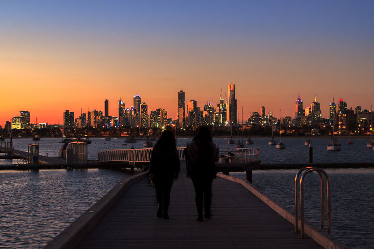 Friends walking on pier over sea against buildings during sunset