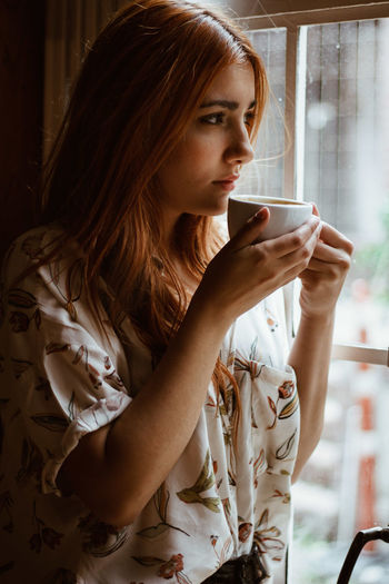 Thoughtful Young Woman Looking Through Window While Drinking Coffee In Cup At Home