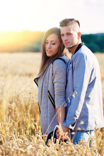Young couple standing on field against sky during sunset