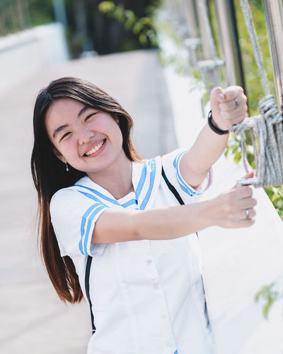 Smiling One Person Happiness Emotion Real People Casual Clothing Lifestyles Standing Leisure Activity Day Teeth Toothy Smile Looking At Camera Young Adult Waist Up Portrait Front View Women Three Quarter Length Outdoors Human Arm Hairstyle Arms Raised