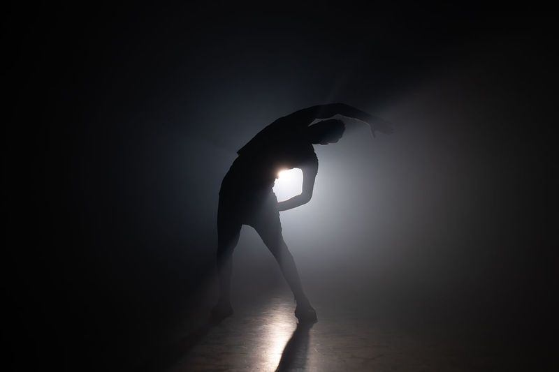 Side view of silhouette woman standing against illuminated light