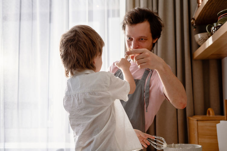 Dad holds a blender and plays with his little son. rubs his nose with whipped cream