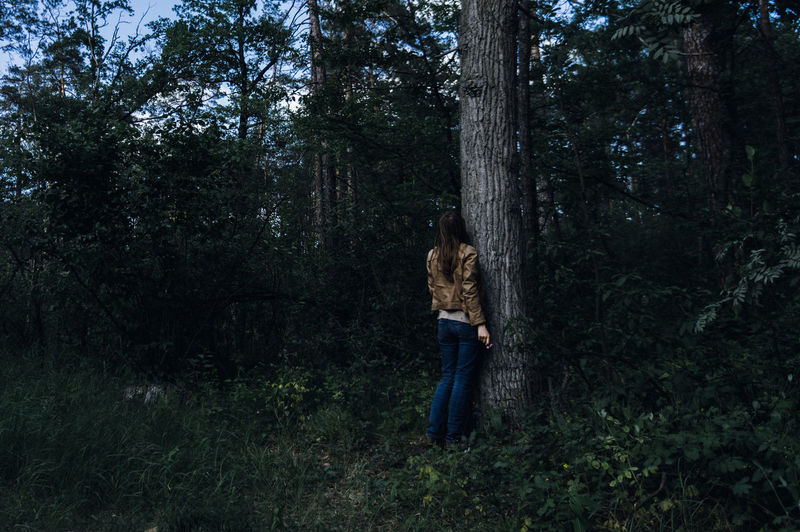 The Sad Alone Woman Staying Under The Tree in the Gloomy Forest Tree Plant Forest Land One Person Tree Trunk Trunk Growth Full Length WoodLand Nature Young Adult Standing Day Leisure Activity Casual Clothing Adult Real People Women Outdoors Jeans Sadness Depression - Sadness Hairstyle Gloomy
