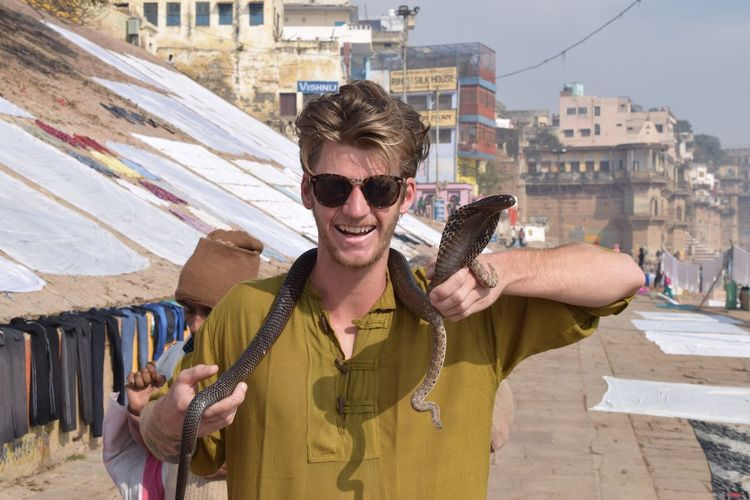 Tourist holding cobra against buildings in city