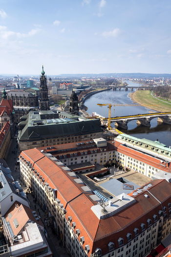 Aerial view of Dresden cathedral of the Holy Trinity with Augustus bridge over Elbe in Dresden, Germany, sunny spring day Dresden Cathedral Holy Trinity Church Royal Court Hofkirche Sanctissimae Trinitatis Bridge Augustus Repair Catholic Religion Crane Elbe River Construction Site Aerial View Real People Restoration Arch Stone History Tourist Famous Landmark Place Germany City Centre Saxony Monument Statue World Man Building Architecture Museum Unesco Gallery Copy Space Vertical