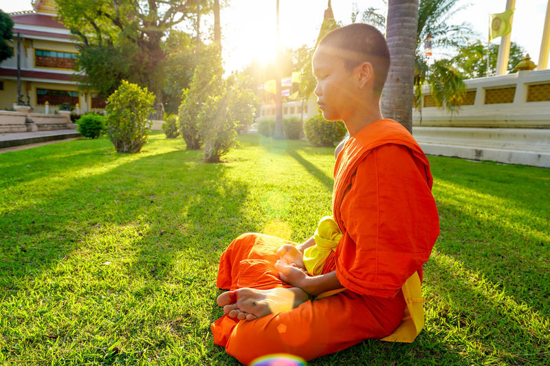 Meditation Architecture Casual Clothing Day Full Length Grass Growth Leisure Activity Lens Flare Lifestyles Males  Meditate On Nature Men Nature One Person Orange Color Outdoors Plant Real People Side View Sitting Sunlight Young Men