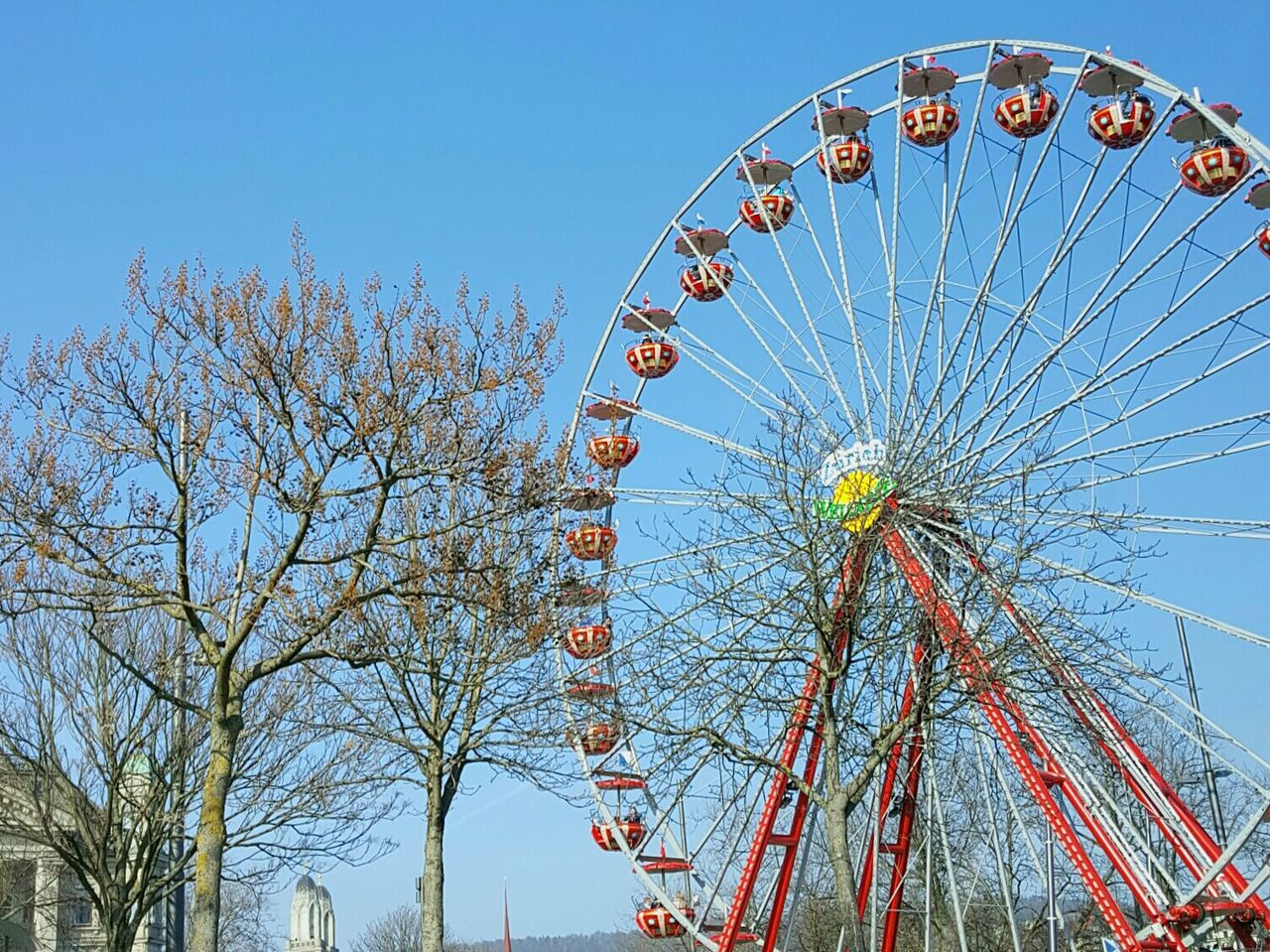 amusement park, arts culture and entertainment, ferris wheel, low angle view, tree, amusement park ride, big wheel, branch, day, no people, clear sky, blue, outdoors, bare tree, sky, nature