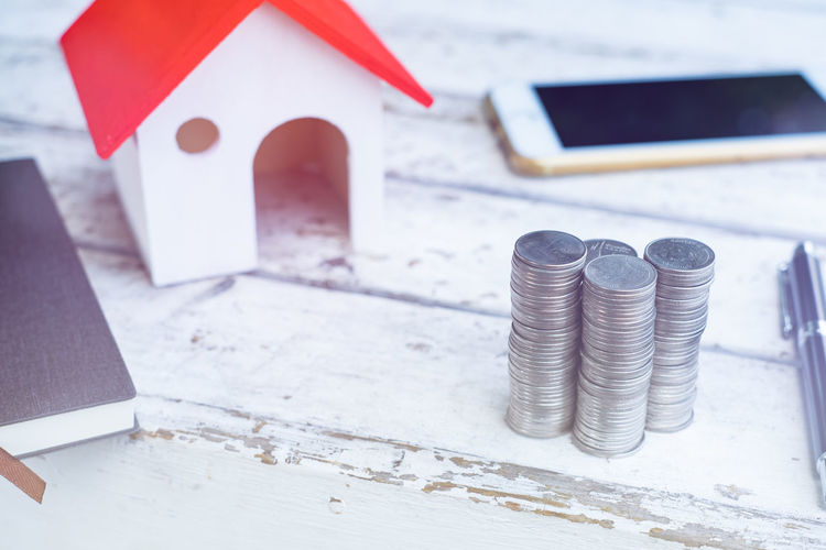 High angle view of stacked coins with model home on table