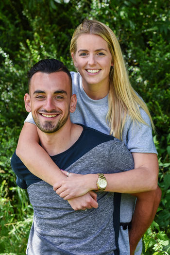 Portrait Of Happy Young Man Piggybacking Girlfriend At Park