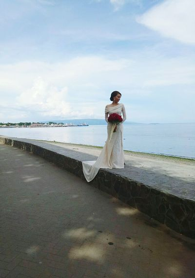 Full Length Of Woman Holding Flower Bouquet By Sea Against Sky