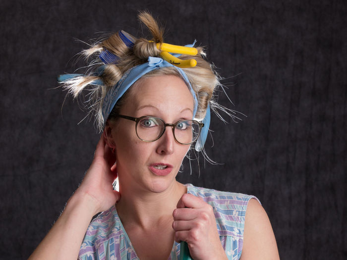 Portrait of woman wearing hair curlers against wall